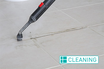 Grout Medic worker cleaning grout in a house