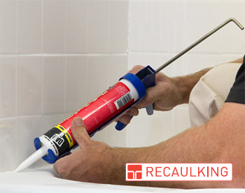 Grout Medic worker recaulking bathtub in bathroom