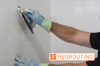 Grout Medic worker regrouting tile in a bathroom