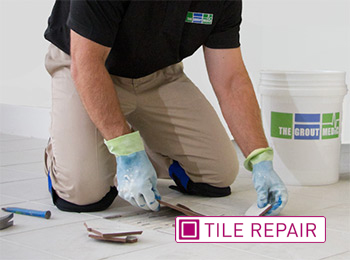 Grout Medic worker repairing tile in a bathroom