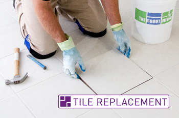 Grout Medic worker replacing tile on a bathroom floor