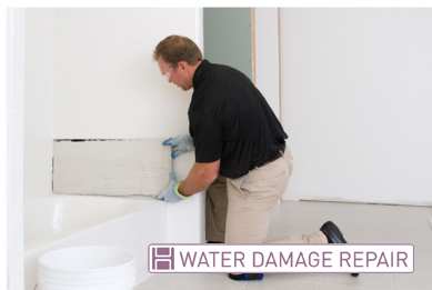 Grout Medic worker repairing water damage in a bathroom